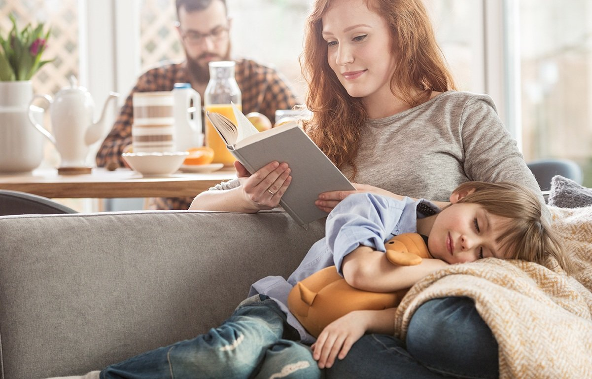 child cuddling on mother's lap while she reads a book on the couch and dad is in the background at the kitchen table