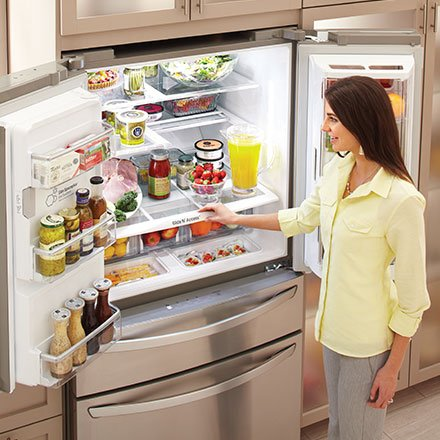 woman staning in front of a fully stocked LG refrigerator