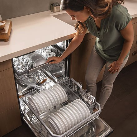 woman emptying dishes in an LG dishwasher