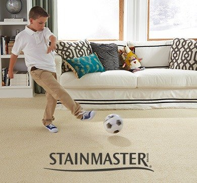 Young boy kicking a soccer ball in a living room with Stainmaster® carpet