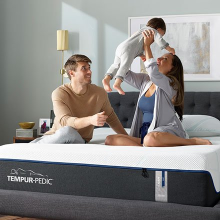 Parents and infant on a Tempur-Pedic mattress