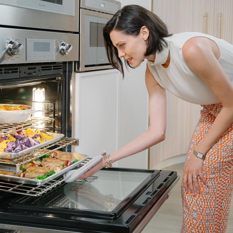 woman cooking with a Thermador wall oven